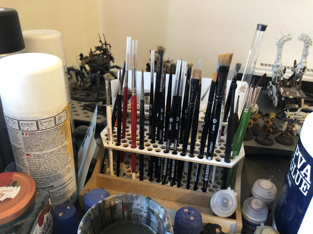 A lot of paintbrushes in a stand on a messy wargaming hobby desk