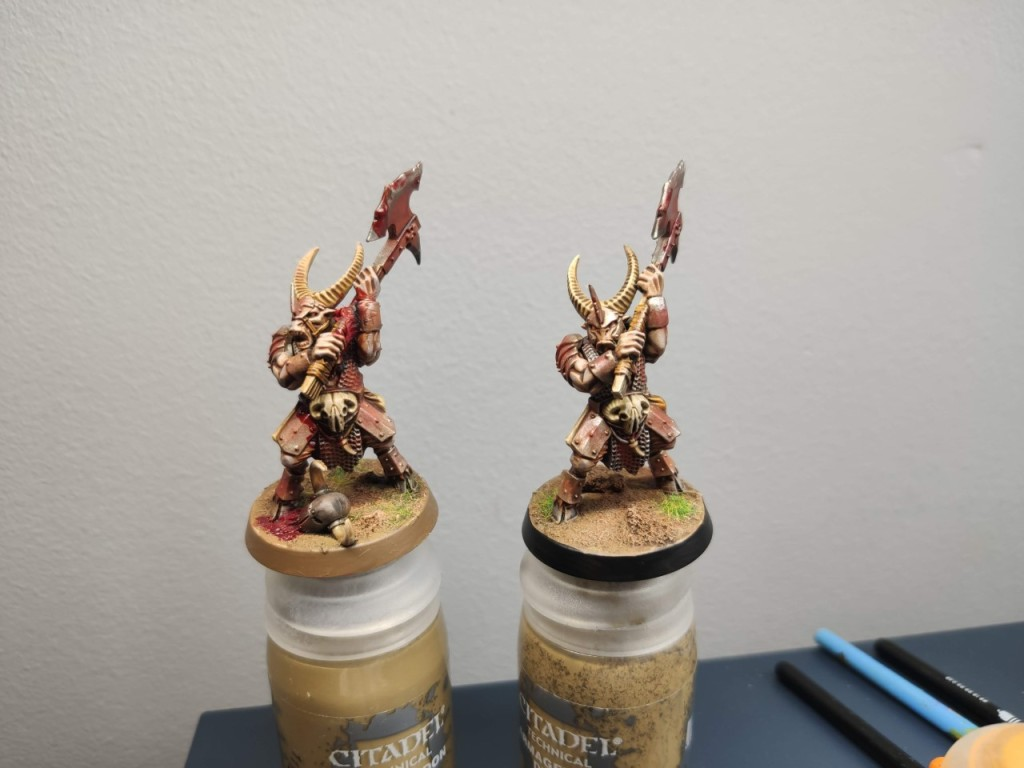 two painted beastmen, one with brown trim on the base and another with black trim